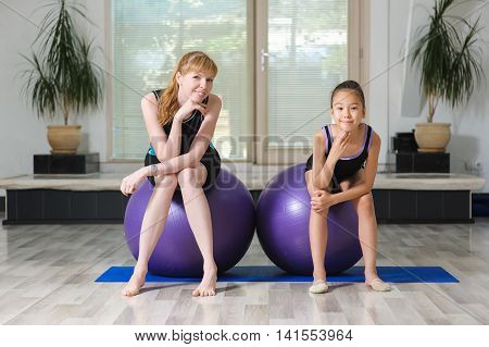 Two girls in the gym. Two pretty sports girls sit on gymnastic balls in the gym. Young japanese girl gymnast and young blonde woman.