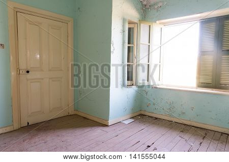 Interior of a dirty damaged abandoned room with open windows and closed door.