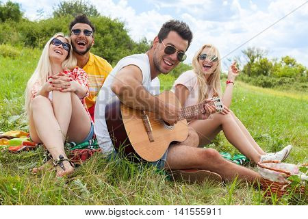 Young people listening guy playing guitar group friends summer day sitting green grass outdoor picnic nature two couple men with girls laugh singing song together