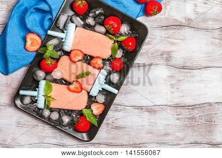 Homemade strawberry ice cream or popsicles on dark wooden table, frozen fruit juice, vegetarian food