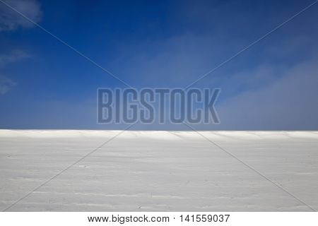 farm field photographed in winter, covered with white snow, blue sky in the background