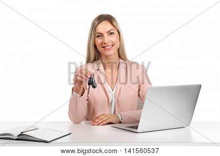Seller woman at table with laptop holding  car key isolated on white
