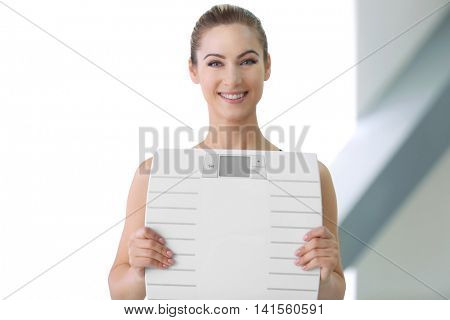 Beautiful young woman holding floor scales on light background