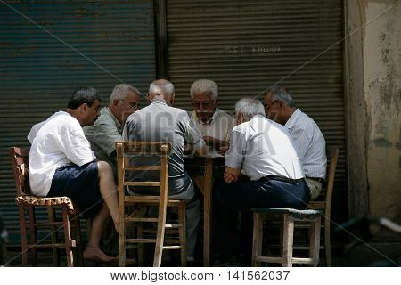 TARSUS, Turkey - JUNE 22, 2016: People sitting and playing cards. Editorial image