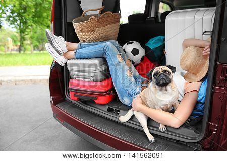 Sleeping girl in car trunk with cute pug and luggage. Travel concept
