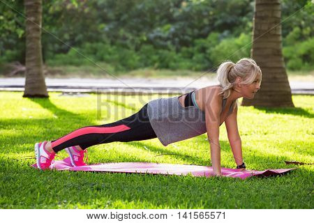 Young Beautiful Fitness Woman With Ponytail Doing Plank Position Outside On The Green Grass