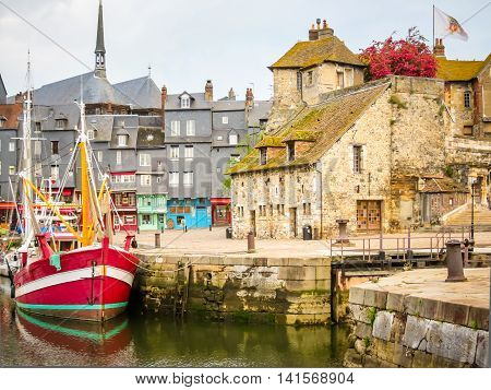 Old boat and medieval Lieutenancy building - entrance to the old harbour. Honfleur, Normandy, France