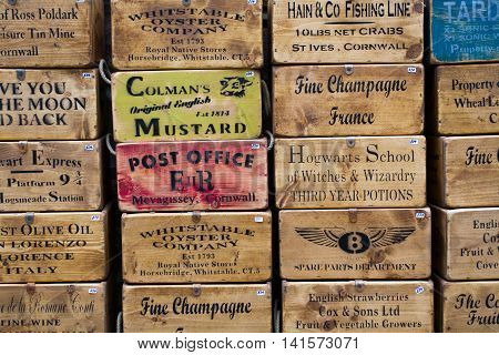 ST IVES, CORNWALL, UK - JUNE 26, 2016. Antique wooden boxes with advertisements and phrases stamped and stencilled on the side forming a background.