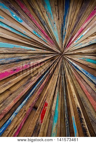 An abstract art background made from strips of colourful wood arranged in a pattern that converges into a central point.