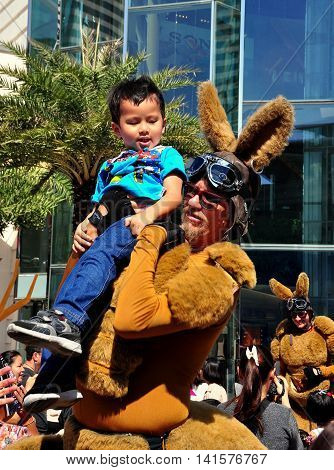 Bangkok Thailand - January 11 2013: Man dressed as a giant Australian kangaroo holds a little Thai boy at the Siam Paragon shopping center plaza on Children's Day *