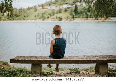 Introverted boy sitting on the bench by the lake