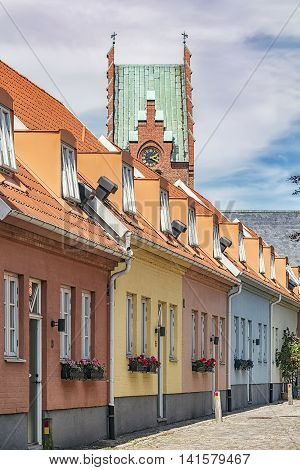 A row of pastel painted houses in Trelleborg Sweden. The church in the background.