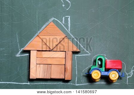 Creative house made of wooden blocks and drawing by chalk colored car toy near on green school blackboard