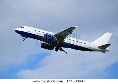 Closeup of flying airplane with blank livery. Travel background with airplane flying in the blue sky.