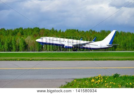 Closeup of flying airplane with blank livery praparing for take off. Travel background with airplane ready to fly in the sky.