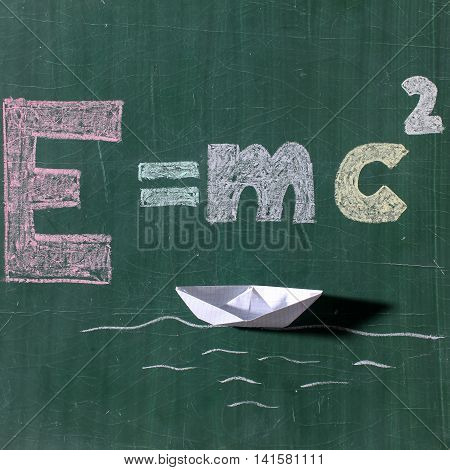 Theory of relativity formula text word drawing by colorful chalks and white boat paper origami on sea waves on school green chalkboard