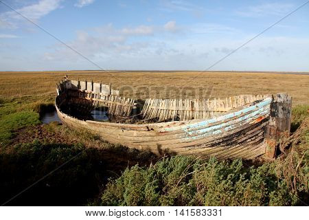 An old wrecked whaler lies in the saltmarshes in East Anglia England amongst a bleak and empty landscape