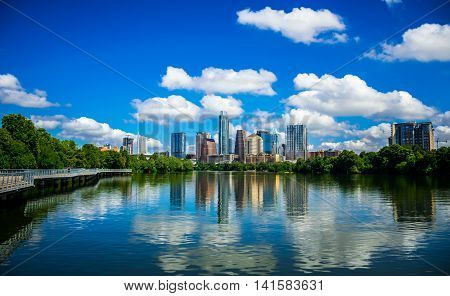 Riverside Pedestrian Bridge Summer time Bliss Reflections on Town Lake Austin Texas Skyline Cityscape. A Wonderful Calm morning on the colorado river mirror reflection of skyscrapers and towers the Capital City in Blue