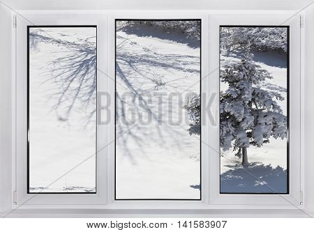 Behind a window winter, and the house warm. Modern plastic Windows