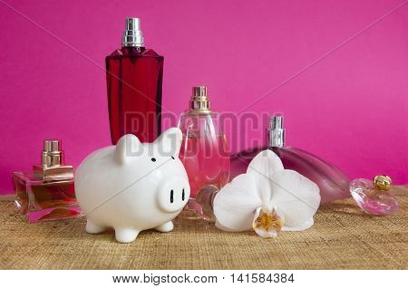 Saving on perfumes - set with piggy bank on pink background