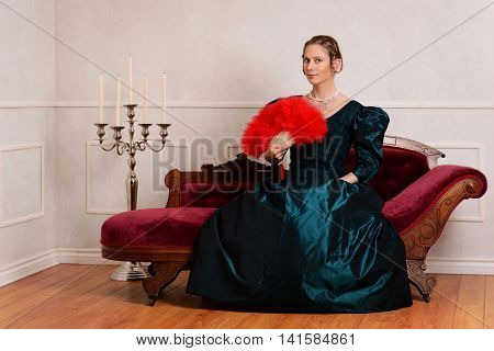 young victorian woman with red fan on couch