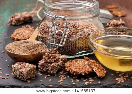 flax seeds and products thereof: linseed oil flax flour energy bars and crackers from flax seeds on a dark a stony background