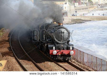 A vintage steam locomotive passes through Dawlish on the famous Brunel railway line