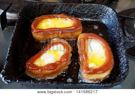 Fried eggs fried in a piece of a white long loaf of bread