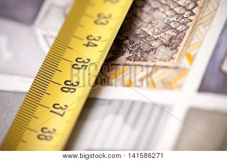 Yellow measuring tape on the background of watercolor floorplan sketch painting symbolising artistic approach in designing and building interior lived space