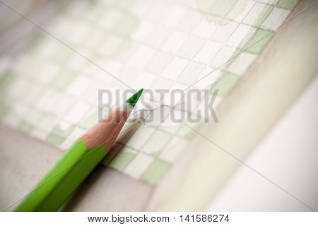 Macro closeup image of light green pencil on splashy illustrated bathroom floor plan with checkers tiling pattern