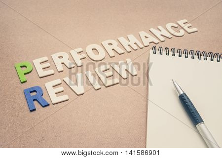 Performance review text with open spiral notebook and pen on brown background - concept of quality measurement