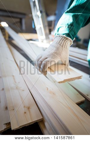 Hand In Fabric Gloves Holding Wooden Plank