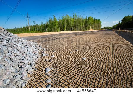 Unfinished Asphalt Country Road In Pine Forest