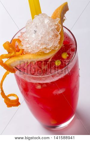 icy blood orange cocktail with slices of blood orange and orange peel selective focus and closeup