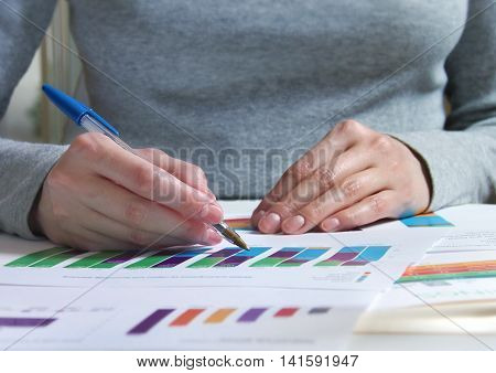 A girl reviewing documents with charts and graphs