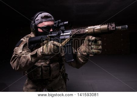 Man with rifle in dark glasses and black mask aiming at target from assault rifle