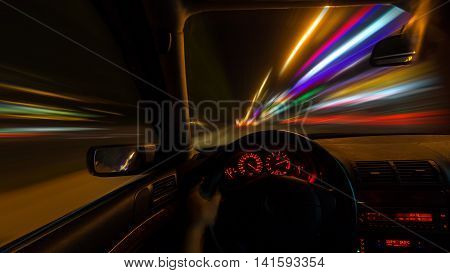 The car moves at great speed at the night. Full throttle. The view through the eyes of the driver