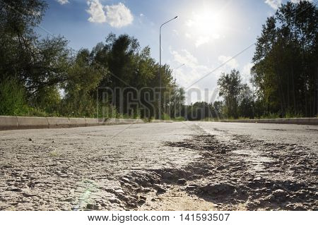 Broken road hole in the pavement. A clear day in summer. Photo is focused on the pit. Trees and sky in the background.