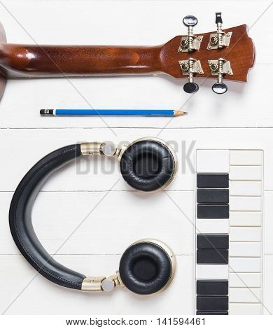 Music Production Equipments on white table. Guitar, small midi keyboard, headphone and pencil can be use for Music writing, Music producing. Music technology make it easier to produce music at home.