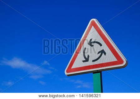 roundabout road sign on blue sky close-up