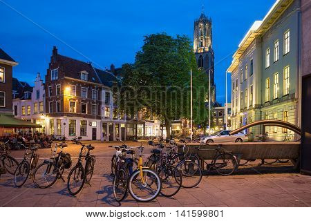 UTRECHT THE NETHERLANDS - JUNE 30: Parked bicycles in the evening near Dom Tower on June 30 2016 in the centre of Utrecht The Netherlands