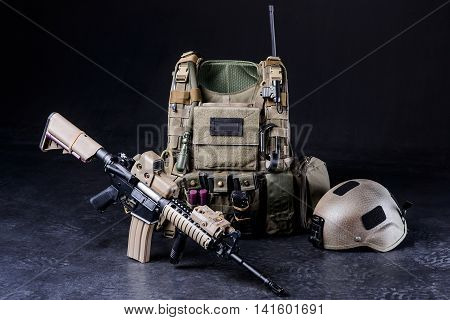 Assault riflebulletproof vesthelmet and other military amunitions on black background