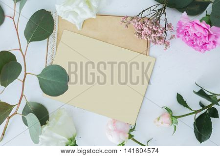 Top view of Wedding background with card. Mock-up for text with free Place. Template invitation white and pink roses and paper papyrus. Falt lay