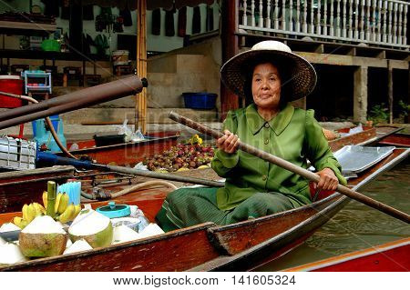 Samut Songkram Thailand - December 27 2005: Woman paddling her boat along a canal selling tropical fruits at the Damnoen Saduak Floating Market
