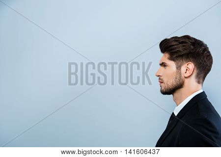 Side View Of Serious Businessman Isolated On Gray Background