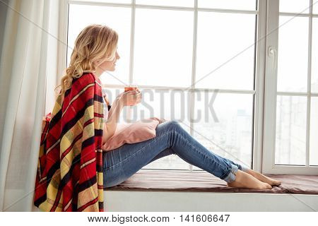 Side View Of Young Woman Sitting On Windowsill And Basking With Plaid And Cup Of Tea