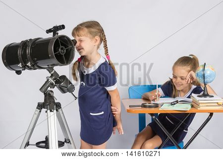 Girl Astronomer Looks Through The Eyepiece Of The Telescope, And The Other Girl Sitting Happily At T