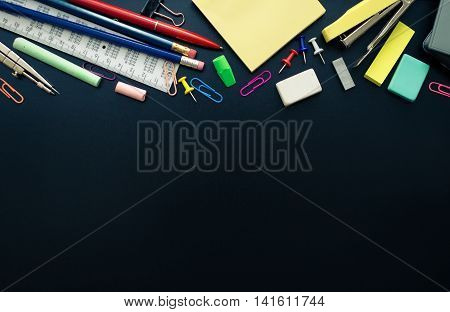 Back to school concept. School supplies on blackboard background with space for text. Back to school concept with stationery. Schoolchild and student studies accessories. Top view.