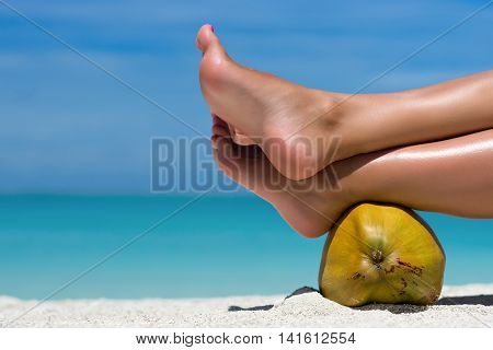 Female Feet Propped On Coconut On The Beach, Blue Sea Background