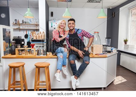 Barista coffee shop owner couple happy smile sitting on bar counter mix race man woman open new small business
